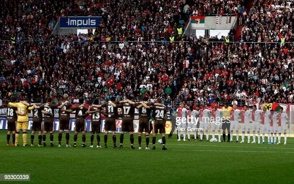 Players observe a minute of silence to commemorate Robert Enke before the Second Bundesliga match between FC Augsburg and FC St Pauli at the Impuls...
