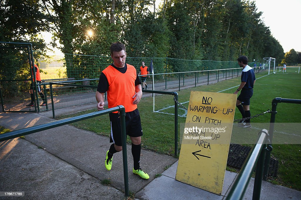 Players of Alresford Town return to the dressing room after warming up ahead of the FA Cup Extra Preliminary Round match between Alresford Town and Winchester City at Alrebury Park on August 16, 2013 in New Alresford, England.
