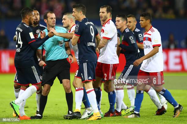 Players of Bayern and Hamburg gather around referee Marco Fritz following a foul of Gideon Jung of Hamburg to Kingsley Coman of Bayern Muenchen...
