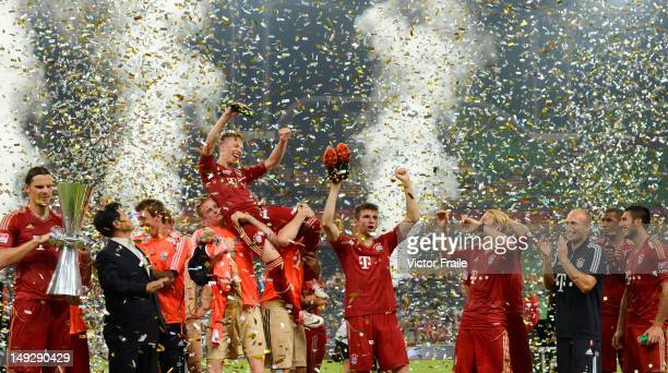 Players of Bayern Muenchen celebrates with the trophy after winning a friendly match against VfL Wolfsburg as part of the Audi Football Summit 2012...