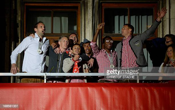 Players of Bayern Munich stand on the balcony of Munich's town hall while celebrating with fans gathered at the Marienplatz the team's German league...