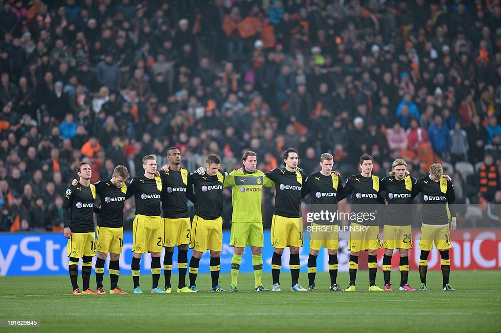 Players of Borussia Dortmund stand to pay tribute to football fans who were on board of an Antonov AN-24 plane which made an emergency landing in Donetsk on February 13, 2013. Five people died when the Antonov AN-24 plane with dozens of football fans on board made an emergency landing in the eastern Ukraine city of Donetsk, officials said. The cause of the accident was not immediately clear but the plane was flying from the southern resort city of Odessa when it overturned and began breaking up upon landing at Donetsk airport, according to the ministry.