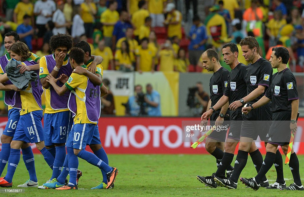 Players of Brazil (L) and the referees of the match leave the field at the end of the FIFA Confederations Cup Brazil 2013 Group A football match between Brazil and Japan, at the National Stadium in Brasilia on June 15, 2013.