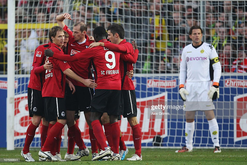 Players of Freiburg celebrate and goalkeeper <a gi-track='captionPersonalityLinkClicked' href=/galleries/search?phrase=Roman+Weidenfeller&family=editorial&specificpeople=726753 ng-click='$event.stopPropagation()'>Roman Weidenfeller</a> of Dortmund reacts after <a gi-track='captionPersonalityLinkClicked' href=/galleries/search?phrase=Mats+Hummels&family=editorial&specificpeople=595395 ng-click='$event.stopPropagation()'>Mats Hummels</a> of Dortmund scored an own goal during the Bundesliga match between SC Freiburg and Borussia Dortmund at the Badenova Stadium on November 20, 2010 in Freiburg im Breisgau, Germany.