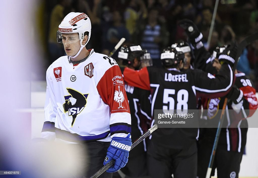 Players of Geneve-Servette are celebrating a goal while Adis Alagic of Villach SV looks disappointed during the Champions Hockey League group stage game between Geneve-Servette and Villach SV on August 23, 2014 in Geneva, Switzerland.