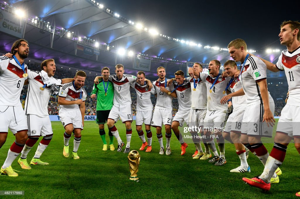 Players of Germany dance around the World Cup trophy in celebraton after the 2014 FIFA World Cup Brazil Final match between Germany and Argentina at Maracana on July 13, 2014 in Rio de Janeiro, Brazil.