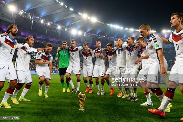 Players of Germany dance around the World Cup trophy in celebraton after the 2014 FIFA World Cup Brazil Final match between Germany and Argentina at...