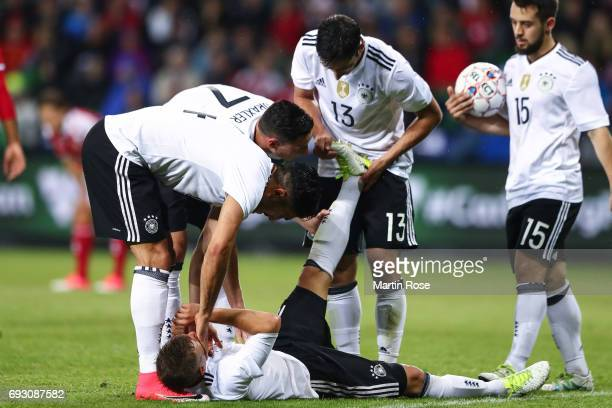 Players of Germany help Joshua Kimmich as he lyes on the ground during the international friendly match between Denmark v Germany on June 6 2017 in...