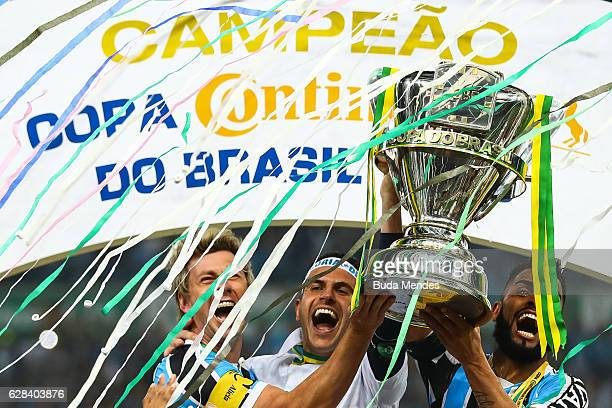 Players of Gremio celebrate the title with the trophy after a match between Gremio and Atletico MG as part of Copa do Brasil Final 2016 at Arena do...