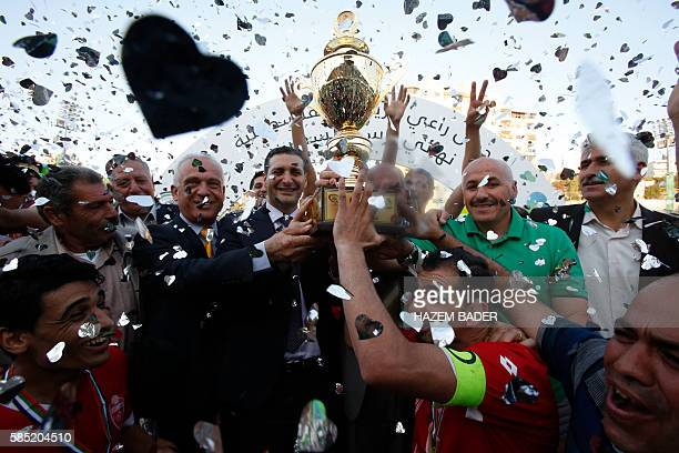 Players of Hebron's Ahly alKhalil football club celebrate with the trophy after beating Gaza's Khan Yunis during the second leg of their Palestinian...