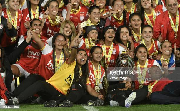 Players of Independiente Santa Fe celebrate with the trophy after winning a second leg match between Independiente Santa Fe and Atletico Huila as...