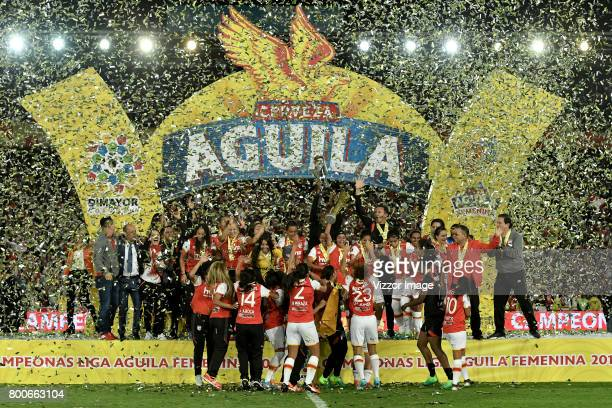 Players of Independiente Santa Fe lift the trophy to celebrate after winning a second leg match between Independiente Santa Fe and Atletico Huila as...