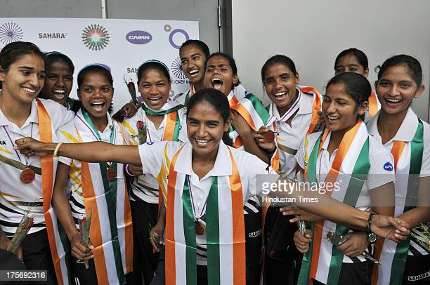 Players of Indian Women's Junior Hockey team which won bronze medal at Junior Hockey World Cup celebrate after their arrival at the Indira Gandhi...