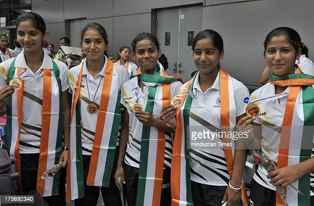 Players of Indian Women's Junior Hockey team which won bronze medal at Junior Hockey World Cup pose with their medals after their arrival at the...