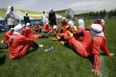 Players of Iran's women national football team listen to instructions before their friendly football match with club Malavan Anzali women's team in...