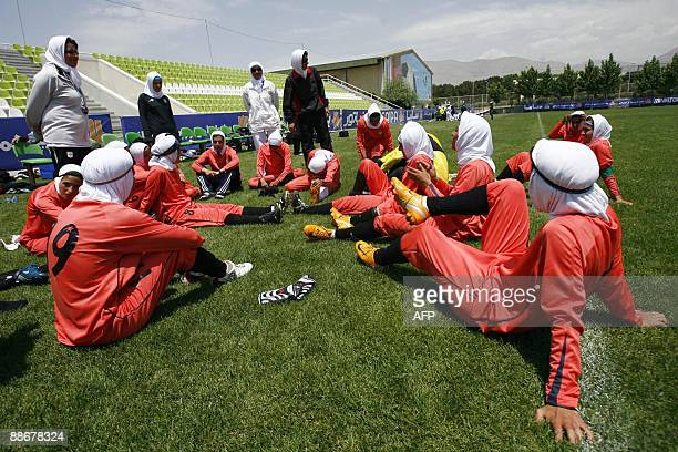Players of Iran's women national football team listen to instructions before their friendly football match with club Malavan Anzali women's team in...