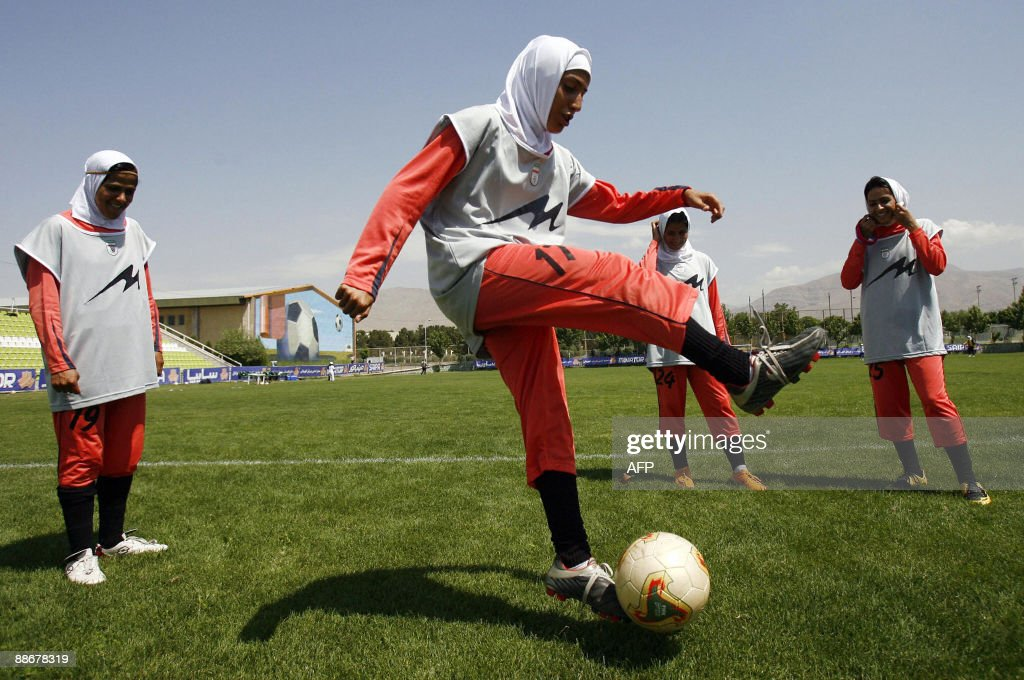Players of Iran's women national football team warmup before their friendly football match with club Malavan Anzali women's team in Tehran on June 25...