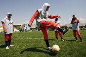 Players of Iran's women national football team warmup before their friendly football match with club Malavan Anzali women's team in Tehran on June 25...