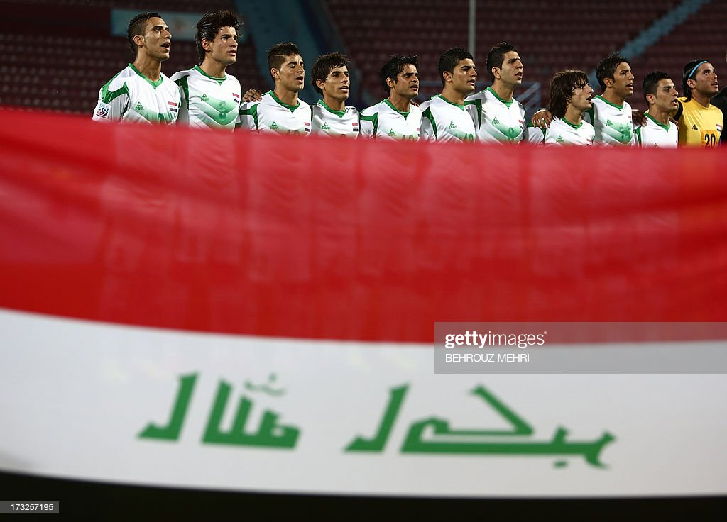 Players of Iraq listen to their national anthem as they stand next to their national flag prior to their semi-final football match against Uruguay at the FIFA Under 20 World Cup at Huseyin Avni Aker stadium in Trabzon on July 10, 2013. AFP PHOTO/BEHROUZ MEHRI +++ RESTRICTED TO EDITORIAL USE +++