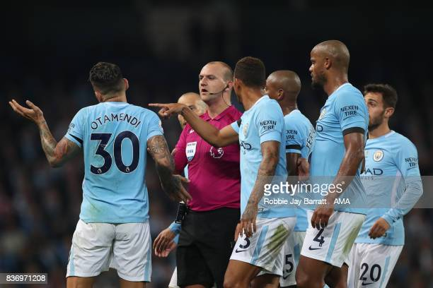 Players of Manchester City surround Referee Robert Madley during the Premier League match between Manchester City and Everton at Etihad Stadium on...