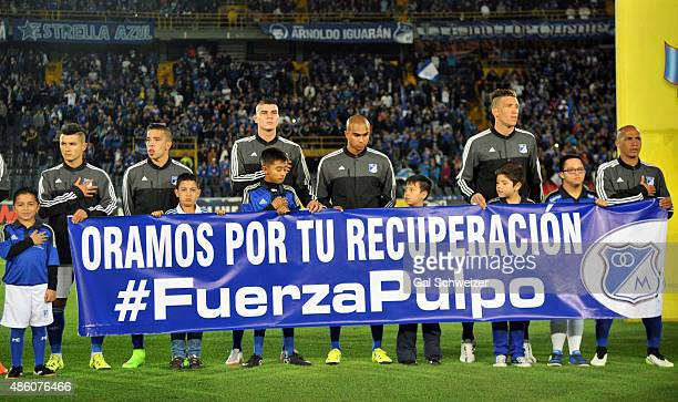Players of Millonarios hold a banner in honor to the Uruguayan goalkeeper Alexis Viera shot and wounded during a robbery in the city of Cali prior to...