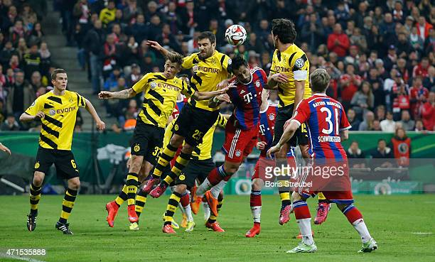 Players of Muenchen and Dortmund jump for a header during the DFB Cup semi final match between FC Bayern Muenchen and Borussia Dortmund at Allianz...
