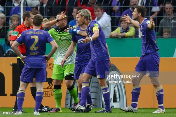 Players of Osnabrueck argue with referee Florian Steuer after his penalty decision during the first round match of the DFB Cup between VfL Osnabrueck...