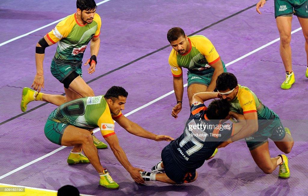 Players of Patna Pirates ( Green ) grab a raider from Bengal Warriors ( Blue ) during Pro Kabaddi league 2016 match at Netaji Indoor Stadium on February 9, 2016 in Kolkata, India.