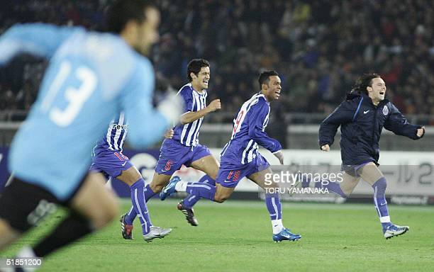 Players of Portugese club FC Porto run toward other teammates on the pitch to celebrate their victory when they defeat Colombian club Once Caldas by...