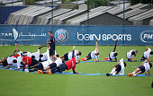 Players of PSG stretch foliowing the first training session of the season for Paris SaintGermain at PSG training camp Centre d'Entrainement Ooredoo...