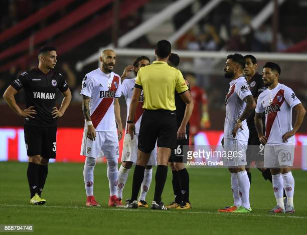 Players of River Plate argue with referee Wilmar Roldan during a second leg match between Lanus and River Plate as part of the semifinals of Copa...