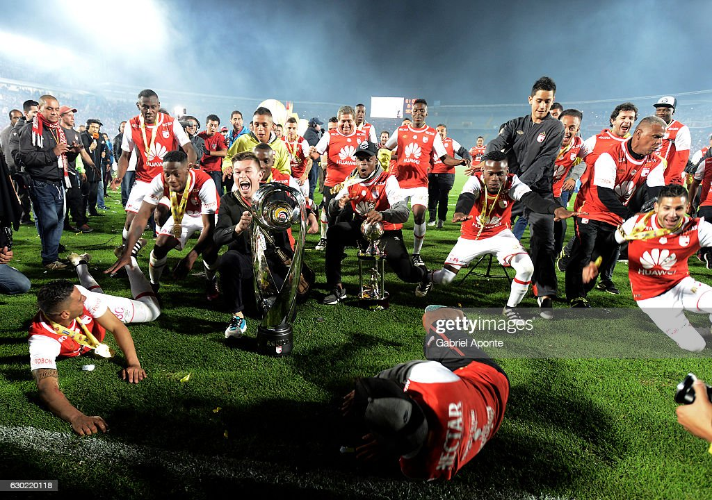 Players of Santa Fe celebrate with the trophy as champions of the Aguila League II 2016 after a second leg final match between Santa Fe and Deportes Tolima as part of Liga Aguila II 2016 at El Campin Stadium on December 18, 2016 in Bogota, Colombia.