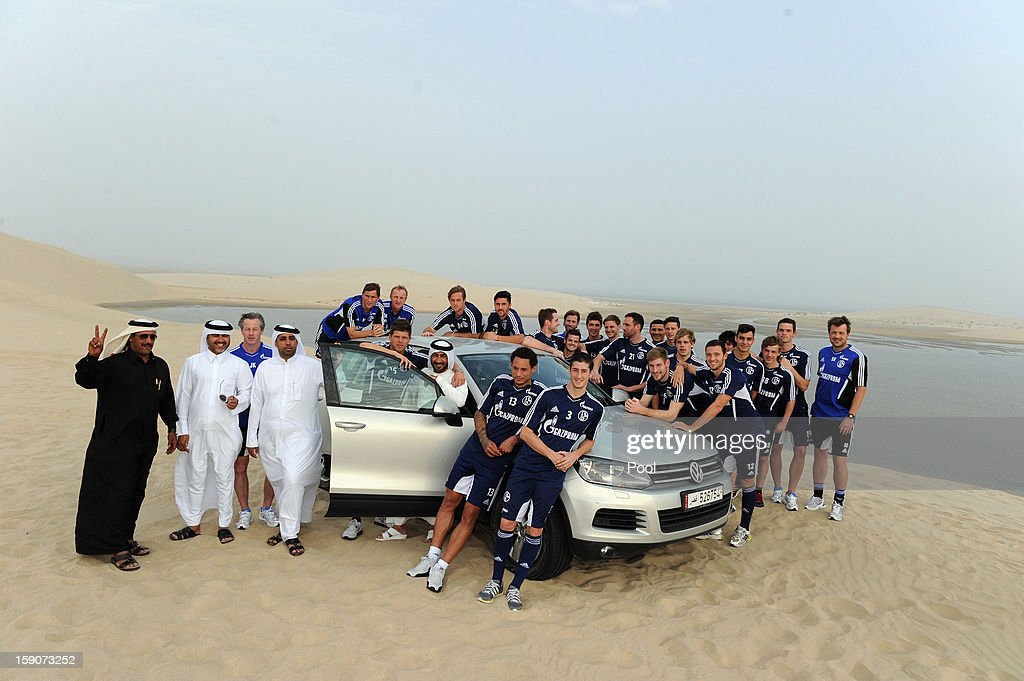 Players of Schalke pose with a VW Tourag during a trip to the desert outside Doha at the Schalke 04 training camp on January 7, 2013 in Doha, Qatar.