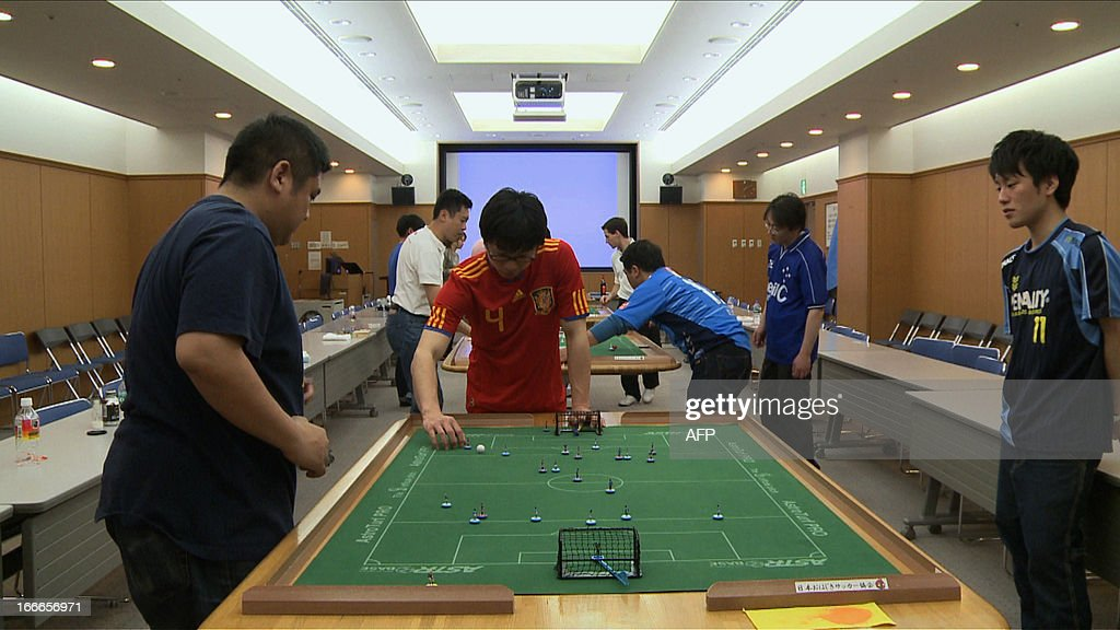 Players of Subbuteo, table football, flick their two-centimetre plastic players to fight for the ball on the table in Yokohama on April 14, 2013. 14 players from the world played on the small fields and Frenchman Cedric Garnier (unseen in this picture) won the annual Yokohama tournament. Fans of Subbuteo from around the world have brought their low-tech table-top sport to high-tech Japan, in the hope of persuading a nation of video gamers to get offline. PHOTO / Antoine BOUTHIER