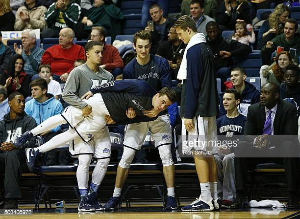 Players of the Monmouth Hawks react on the bench after a basket during the first half of a college basketball game against the Canisius Golden...