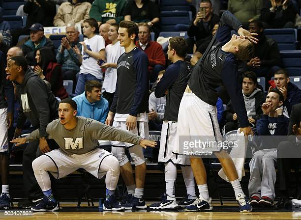 Players of the Monmouth Hawks react on the bench after a basket during the second half of a college basketball game against the Canisius Golden...