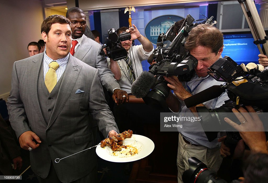 Players of the New Orleans Saints, Zach Strief (L) brings out samples of seafood from the Gulf of Mexico for member of media to taste as <a gi-track='captionPersonalityLinkClicked' href=/galleries/search?phrase=Bobby+McCray&family=editorial&specificpeople=2097156 ng-click='$event.stopPropagation()'>Bobby McCray</a> (2nd L) looks at the White House briefing room following a reception for the 2010 National Football League Super Bowl champions August 9, 2010 in Washington, DC. The Saints, lead by head coach Sean Payton, finished the 2009-2010 season with a winning record of 13-3 and defeated the Indianapolis Colts to take the championship.