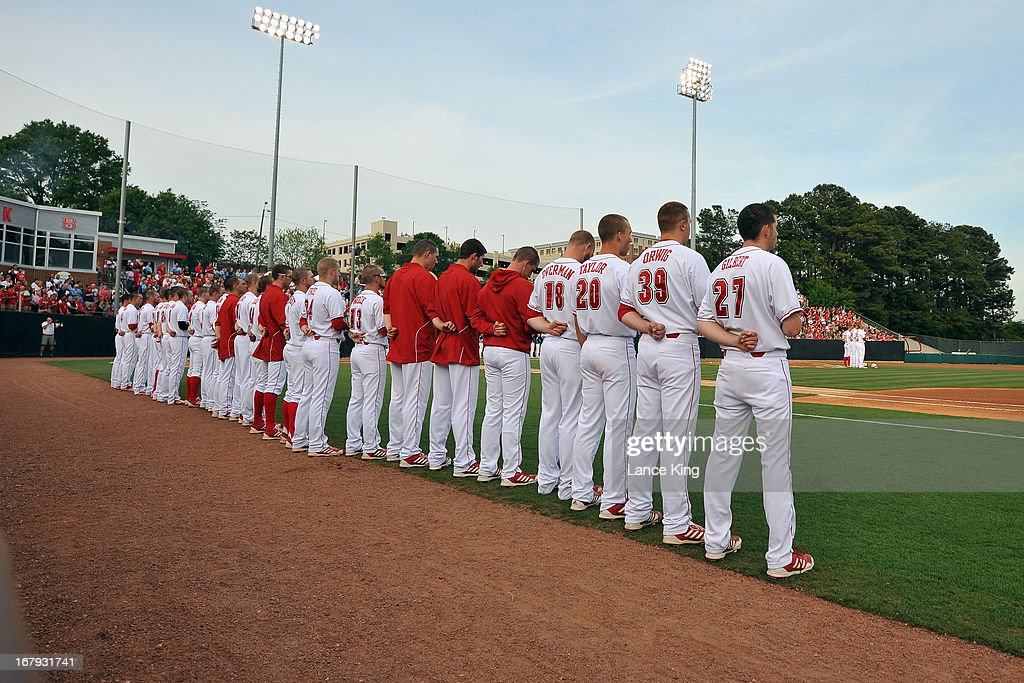 Players of the North Carolina State Wolfpack stand at attention during the Nation Anthem prior to their game against the North Carolina Tar Heels at Doak Field on April 26, 2013 in Raleigh, North Carolina. North Carolina defeated NC State 7-1.