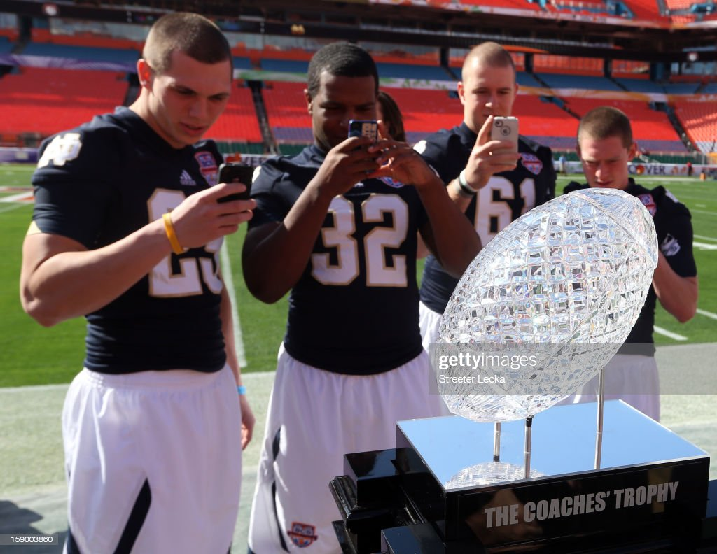 Players of the Notre Dame Fighting Irish take pictures of the National Championship trophy during Media Day ahead of the Discover BCS National Championship at Sun Life Stadium on January 5, 2013 in Miami Gardens, Florida.