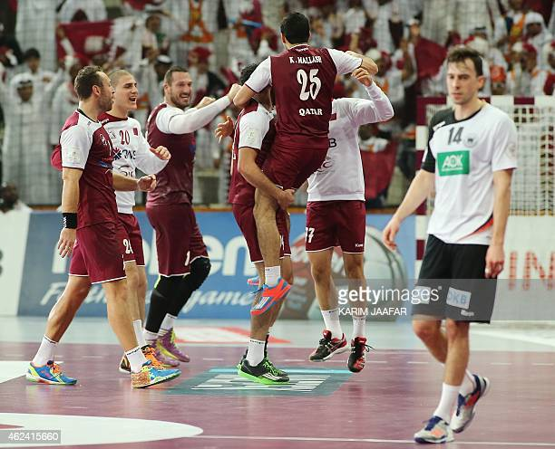 Players of the Qatari national team celebrate their win during the 24th Men's Handball World Championships quarterfinals match between Germany and...