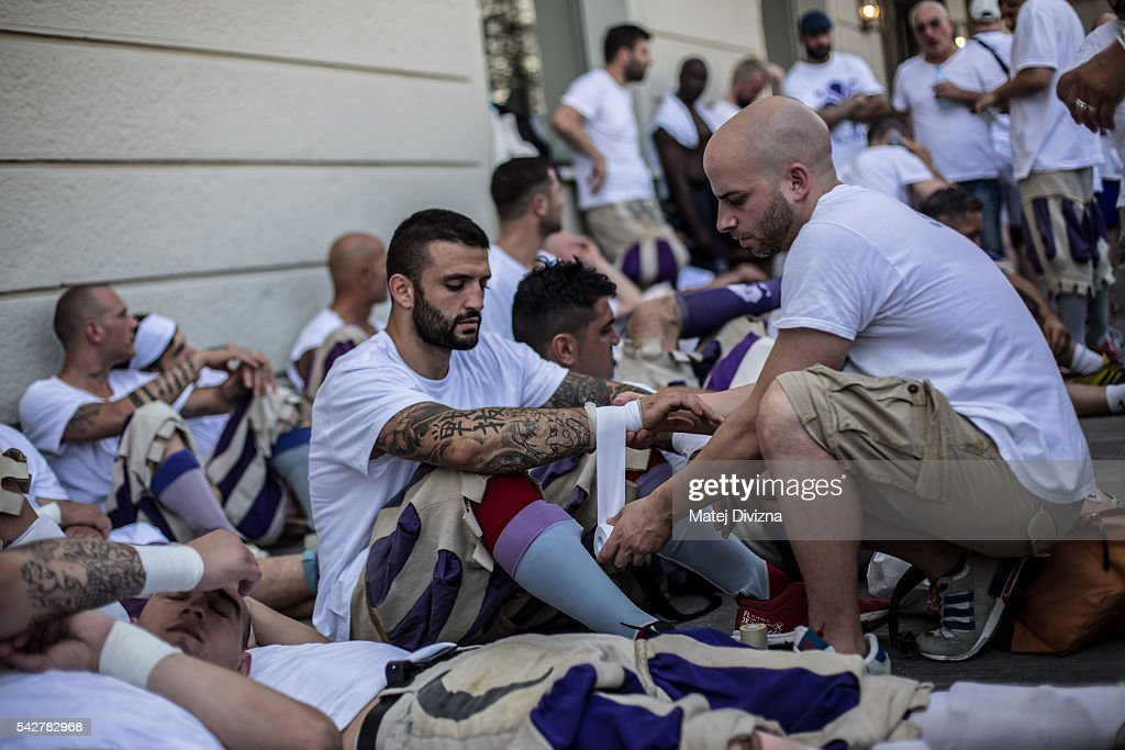Players of the Santo Spirito Bianchi Team prepare before the final match of The Calcio Storico Fiorentino between the Santo Spirito Bianchi (White) Team and the La Santa Croce Azzuri (Blue) Team in the street on June 24, 2016 in Florence, Italy. The Calcio Storico (Historical Football in English) Fiorentino is an early form of football, originating in the 1500's. It is a combination of football, rugby and wrestling. Now, annually during a weekend in early June, four teams representing the districts of Florence face each other in the first semi-finals. The winners go to the final, played every year on June 24, the day of the patron of Florence, St. John the Baptist. The official rules of calcio (football) were written for the first time in 1580 by Giovanni de Bardi, a count from Florence. The teams are formed by 27 players and the ball can be played either with hands or feet. Tactics such as punching, elbowing and all martial arts techniques are allowed but kicks to the are forbidden, as are fights of two or more against one. There is a referee, a field master, and six linesmen. The game lasts 50 minutes, and the winning team is the one who scores most points. The playing field is a giant sand pit with a narrow split constructing the goal running the width of each end. The Calcio Storico was not played for 200 years, until its revival in 1930.