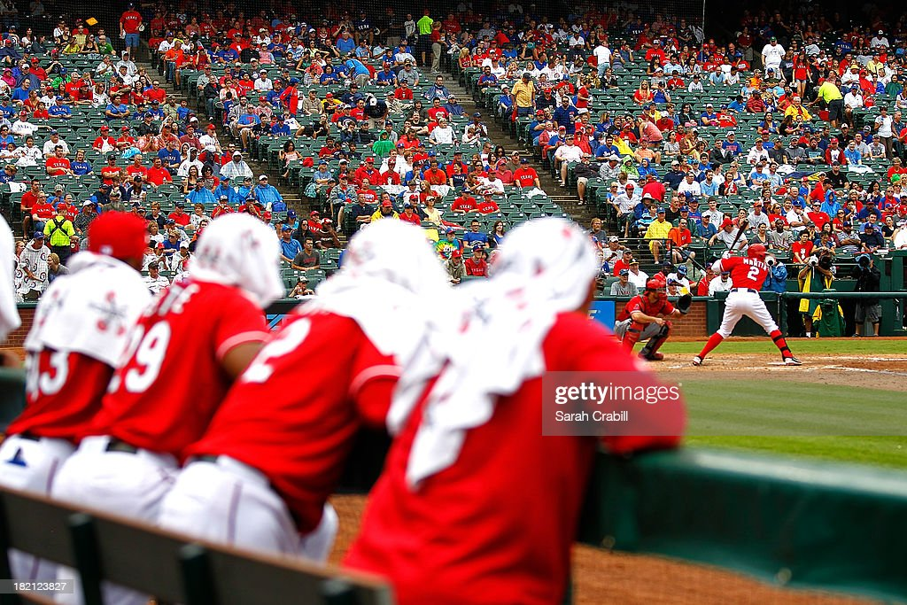 Players of the Texas Rangers look on from the dugout as Leonys Martin #2 bats during a baseball game against the Los Angeles Angels of Anaheim at Rangers Ballpark in Arlington on September 28, 2013 in Arlington, Texas.