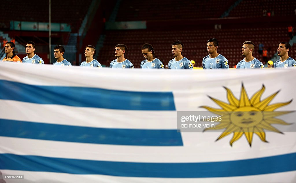 Players of Uruguay listen to their national anthem as they stand next to their national flag prior to their Semi-Final football match against Iraq at the FIFA Under 20 World Cup at Huseyin Avni Aker stadium in Trabzon on July 10, 2013. AFP PHOTO/BEHROUZ MEHRI +++ RESTRICTED TO EDITORIAL USE +++