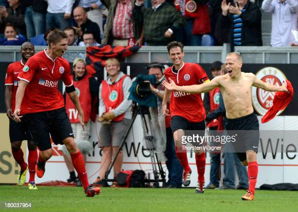 Players of Wiesbaden celebrate after Alex Nandzik is scoring the second goal during the Third Bundesliga match between SV Wehen Wiesbaden and MSV...