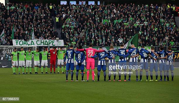 Players of Wolfsburg and Berlin stand for a minutes silence for the Chapecoense football club after the plane crash tragedy before the Bundesliga...