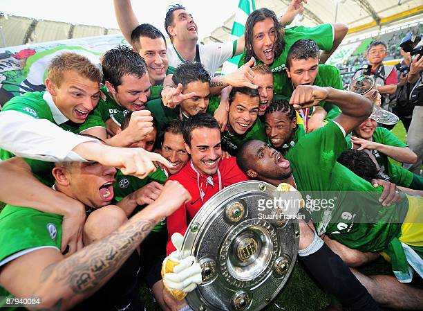 Players of Wolfsburg celebrate the German championship with the trophy after their Bundesliga match against SV Werder Bremen at Volkswagen Arena on...