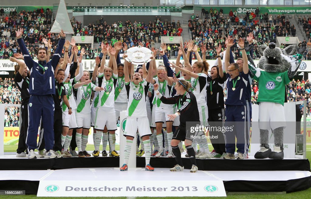 Players of Wolfsburg celebrate with the trophy on the podium after winning the German championship after the Women's Bundesliga match between VfL Wolfsburg and SC Bad Neuenahr at Volkswagen Arena on May 12, 2013 in Wolfsburg, Germany.
