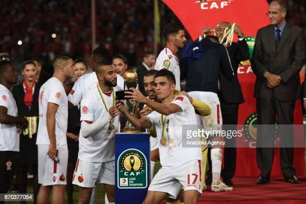 Players of Wydad Casablanca pose for a team photo with the trophy after winning 10 in the CAF African Champions League match against Al Ahly at the...