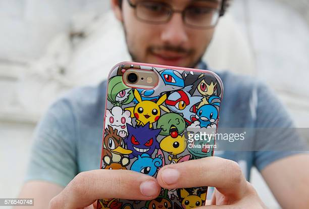 A player's phone is decorated with Pokemon stickers as he plays Pokemon Go a mobile game that has become a global phenomenon the day after it's UK...