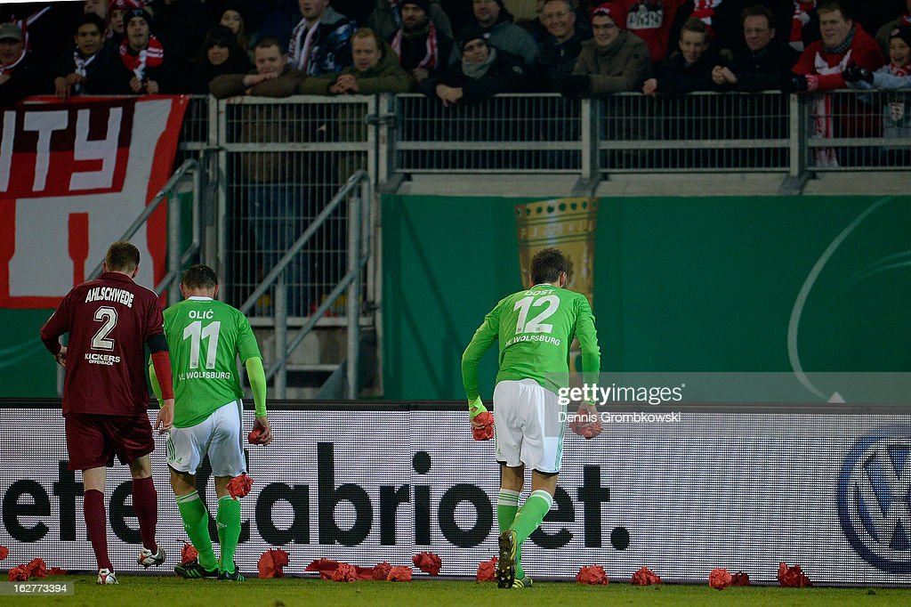 Players pick up paper balls thrown by Offenbach supporters during the DFB Cup match between Kickers Offenbach and VfL Wolfsburg on February 26, 2013 in Offenbach, Germany.